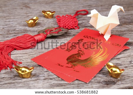 Origami chicken with chinese new year red packets with wishes in mandarin. 2017 is known to be the year of the chicken according to chinese zodiac.