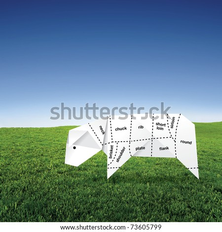 origami cow on grass field with meat specification - stock photo