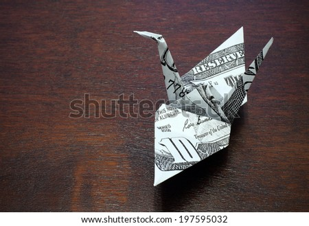 origami crane from a money note on wood table - stock photo