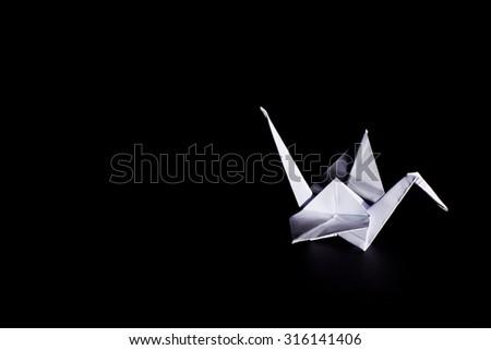 Origami crane isolated on dark background - stock photo