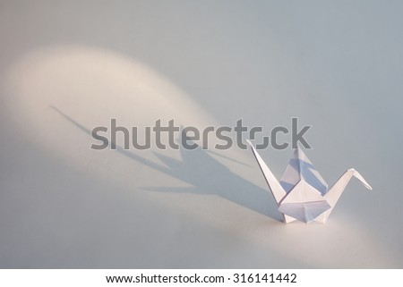 Origami crane isolated on white background with long shadow. - stock photo