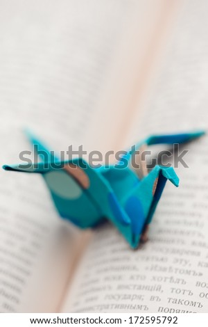 Origami crane lying on open book, selective focus - stock photo