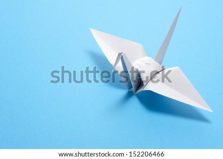 origami crane on blue background - stock photo