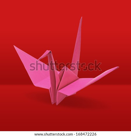 Origami crane on red background - stock photo