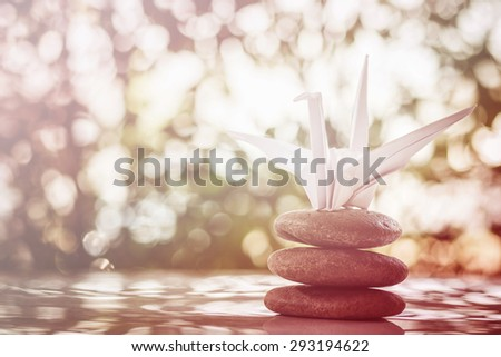 Origami crane, paper bird and zen stones on bokeh background. shallow deep of field and vintage process - stock photo