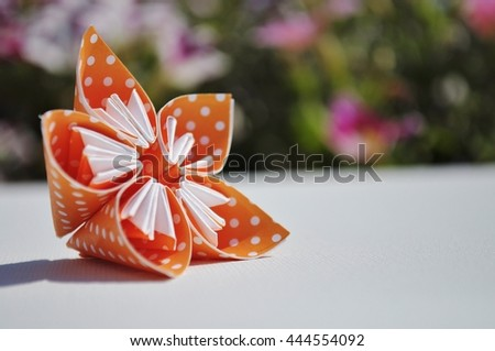 Origami flower made of polka dotted paper. Floral background. Space for text. - stock photo