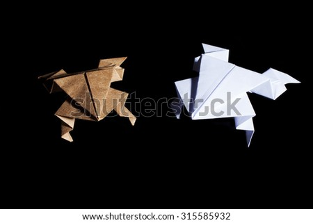 Origami frogs made from white and brown paper on black background. - stock photo