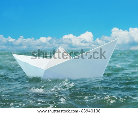 Origami paper boat floating in a sea - stock photo