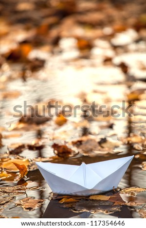 Origami paper boat in a water and fall leaves - stock photo