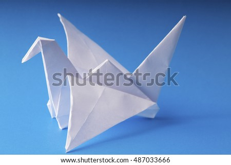 origami paper crane on blue background