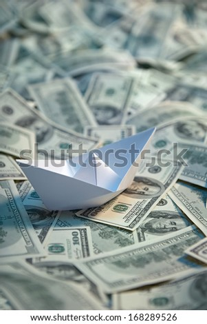 Origami paper ship at sea of money / studio photography of american moneys of hundred dollar on background  - stock photo