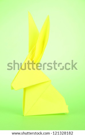 Origami rabbit on green background