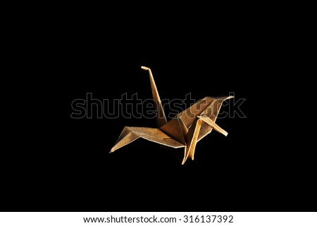 Origami recycle paper crane on wooden background with shadow. - stock photo
