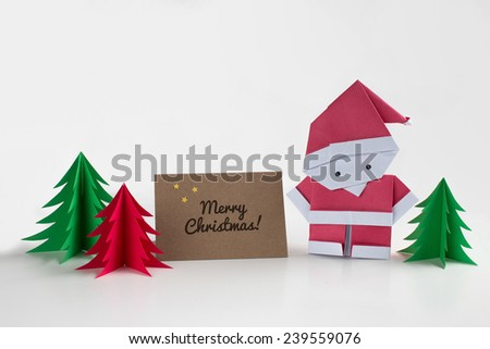 Origami Santa Claus paper craft with christmas trees and a merry christmas card - stock photo