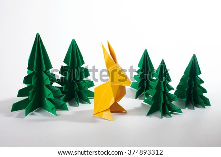 Origami Scene Of A Yellow Bunny Rabbit With Green Trees On White Background