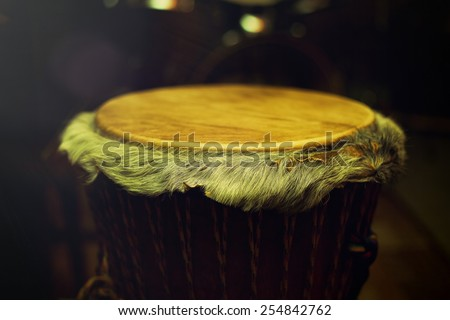 Original african djembe drum with leather lamina with beautiful hair in beautiful tyellow light with dark background - stock photo