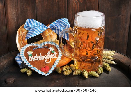 original bavarian Oktoberfest big soft pretzel with beer mug, hops and gingerbread heart from Germany on old beer barrel - stock photo