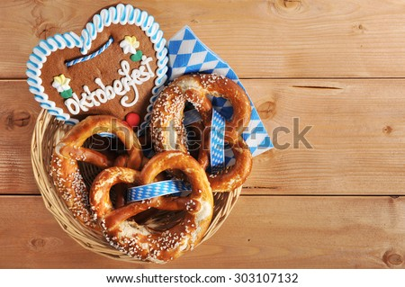 original bavarian Oktoberfest salted soft pretzels with gingerbread heart in a basket from Germany on wooden board