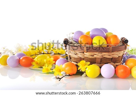 original easter eggs in yellow, violet and orange with flowers and easter nest on white background - stock photo