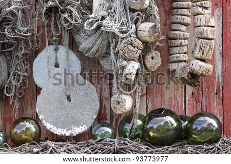 Original fishing nets, stone sinkers and glass floats at boathouse wall in Norway - stock photo