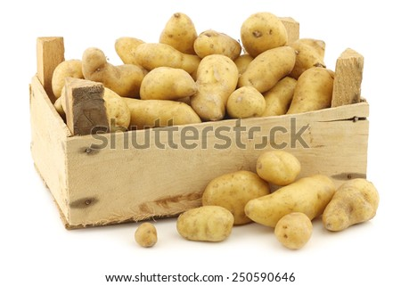"original french ""ratte""potatoes (Solanum tuberosum) in a wooden crate on a white background - stock photo"