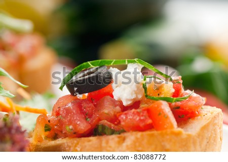 original Italian fresh bruschetta,typical finger food, with fresh salad and vegetables on background - stock photo