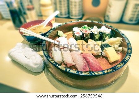 Original plate of nigiri at japanese restaurant in Tokyo city - Vintage filtered look with soft focus on central part of sushi composition - Concept of world gastronomy and local traditional cuisine - stock photo