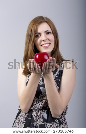 Original sin temptation. Conceptual image of beautiful young smiling joyful woman gives holds red bright apple toward us casual dress smiling and happy brunette grey background  - stock photo