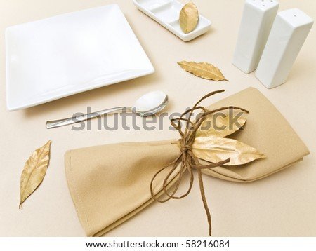 original table serving with golden bay leaves and serviette with cord at beige - stock photo