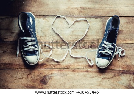 Original Valentine's Day love concept with black sneakers. Studio shot on a wooden floor background.