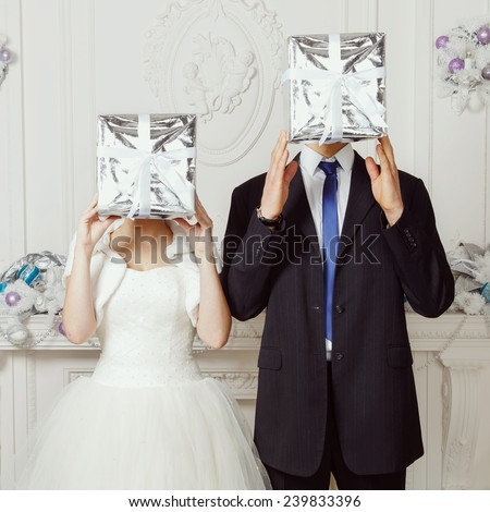 Original wedding, bride and groom cover their faces gift. Happy bride and groom. Bride and groom, original wedding. Wedding, love, groom, bride, gift, day, gift box - holiday concept. Wedding Planner. - stock photo
