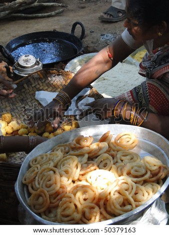 ORISSA INDIA - NOV 10  : An unidentified  woman prepares fried food for snacks at a  weekly market on Nov 10, 2009 in Orissa, India - stock photo