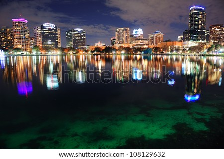 Orlando downtown skyline over Lake Eola at dusk with urban skyscrapers and lights. - stock photo