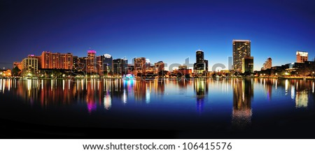 Orlando downtown skyline panorama over Lake Eola at night with urban skyscrapers and clear sky. - stock photo