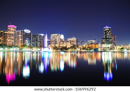 Orlando downtown skyline panorama over Lake Eola at night with urban skyscrapers, fountain and clear sky. - stock photo