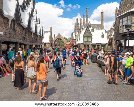 ORLANDO,USA - AUGUST 24, 2014 : Visitors enjoying the Harry Potter themed attractions and shops at the  Hogsmeade Village inside Universal Studios Islands of Adventure theme park - stock photo