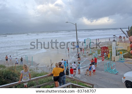 ORMOND BEACH, FL - AUGUST 25: Residents watch the ocean breach the beach driving ramp as Hurricane Irene passes off the coast on August 25, 2011 in Ormond Beach, Florida . - stock photo