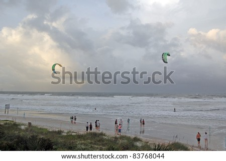 ORMOND BEACH, FL - AUGUST 25:  Spectators watch two unidentified kite-boarders as Hurricane Irene passes off the coast on August 25, 2011, in Ormond Beach, Florida. - stock photo