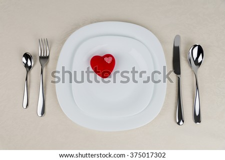 Ornament heart on a white plate on table setting