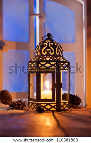 Ornamental Christmas lantern with a glowing candle illuminating a window in the evening light