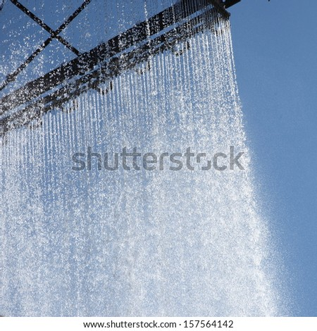 Ornamental curtain of running water on the outside of a corporate building with water droplets glistening in the son