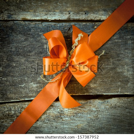 Ornamental diagonal orange ribbon and decorative bow on rustic dark textured wood with copyspace for your greeting or Christmas wishes - stock photo