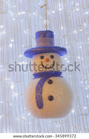 Ornamental snow man doll hanging on Christmas tree - stock photo