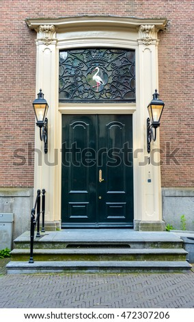 Ornate black door with stonework surround, two lantern light fittings and intricate wrought ironwork decorated with a bird in an old brick exterior wall