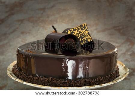 Ornate chocolate cake over dark slate background. - stock photo