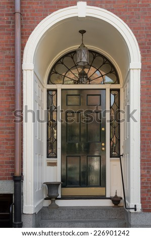 Ornate Entryway with Shiny Black Front Door, Overhead Lunette, and Hanging Lamp in White Archway of Brick Building - stock photo