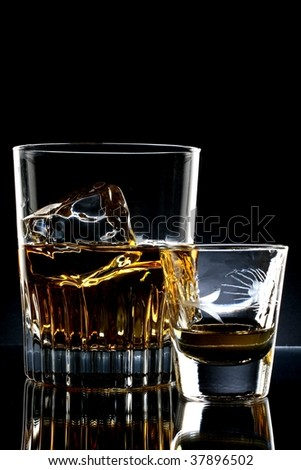 Ornate glass of whiskey and ice and shot glass against black background. - stock photo