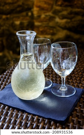 Ornate pitcher with cold white wine and two empty glasses on wicker table in front of rough stone wall in rustic restaurant. Reflection. A game of light and shadow. Selective focus on the pitcher. - stock photo