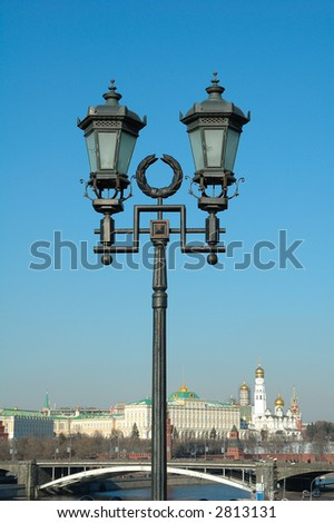 ornate street lamp with a view of old city on the background