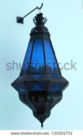 Ornate traditional blue moroccan lamp hanging from a stucco wall - stock photo